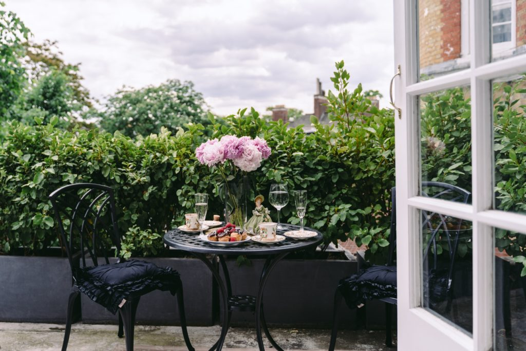 A vase of flowers sitting on a chair in front of a window